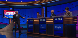 Alex Trebek points at Kevin Bohannon's podium on the April 15, 2019 episode of Jeopardy!, signalling that he has control of the board. Note the white light at the bottom left of the podium.