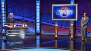 Jeff Rich's contestant photo with Alex Trebek. Alex is at his lectern, Rich is standing well away beside a television screen with the new Jeopardy! logo.